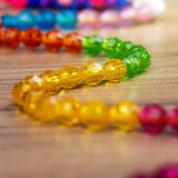 Snake of colored beads on a wooden background Stock Images