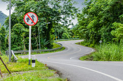 Snake curved road and warning sign Stock Photo