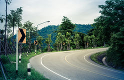 Snake curved road and warning sign Royalty Free Stock Photography