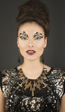 Snake eyes girl. High fashion glamour model with gold dress & make up royalty free stock photography