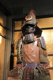 Snake eyes. Samurai armor Tosei-gusoku with punched on the chest plate of the hieroglyph fire inside and helmet Eboshi-nari-kabuto with Maedate in the form of royalty free stock image