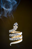 Snake Gemstone Ring and Smoke. Gold ring shaped like a snake and studded with precious gemstones. Smoke in the dark background stock photography