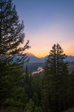 Snake River Sunset in Wyoming. The Grand Teton range and Snake river visible through the pine trees in the foreground at sunset Royalty Free Stock Photography