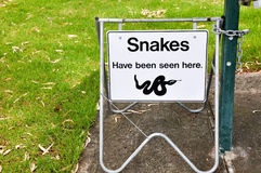 Snake Warning. Sign hanging on metal frame in park setting royalty free stock photography