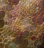 Snakeskin Pebble Patterned Background. A background in shades of deep red and brown.  This pattern resembles a pebble strewn path and also the skin of a lumpy Stock Photos