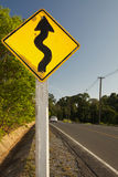 Snaking Road. A traffic sign saying lots of turns ahead. this particular sign is interesting as it was drawn by hand Stock Photo