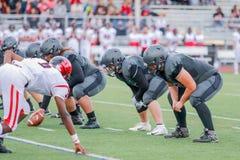 High school football game at snap. The snap at the beginning of a High School Football game stock photo