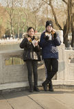 Snap portrait of children. Two children in coat are eating and drinking in a bridge in Beijing, China Royalty Free Stock Image