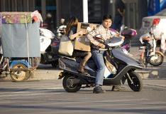 Snap portrait of a drivng couple. A man in countryside is driving a motocycle and waiting for trafficlight on road with his wife carried behind and a package of Royalty Free Stock Photos