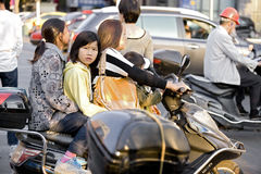 Snap portrait of a drivng mother. A middle aged mother in countryside is driving a motocycle in a bussy traffic area carrying a sisiter and two children  with Royalty Free Stock Photography
