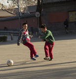Snap portrait of foot ball playing boys. Two boys are playing football on ground for fun before groups of historical buildings of Gulou in Beijing,China royalty free stock images