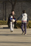 Snap portrait of foot ball playing boys. Two boys in opening coat are playing football on ground happily stock photo