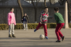 Snap portrait of foot ball playing. A girl and several boys are palying foot ball on a ground happily stock photography