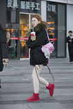 Snap portrait of a girl. A girl is passing by a dress shop and drinkng Royalty Free Stock Photo