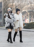 Snap portrait of girls. Two girls in light coat and skirt are walking Royalty Free Stock Images