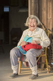 Snap portrait of a laughing senior woman. A village senior woman in grey white hair sitting in chair by home door is weaving sweater and laughing in evening stock photo