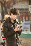 Snap portrait of a male traveler. A boy traveler in coat is sightseeing and taking picture before a dimmed ancient building near famous Gulou Street in Beijing Stock Photography