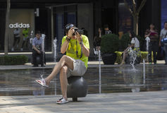 Snap portrait of man photographer. A man photographer in shirt is sitting on a ball and taking picture in a shopping area Stock Image