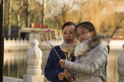 Snap portrait of miss travelers. Two girls in coat are taking self picture by Houhai lake in Beijing, China royalty free stock image