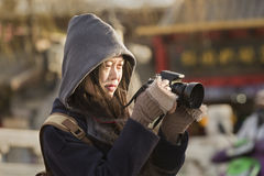 Snap portrait of a miss traveling photographer. A girl in dark coat is taking picture on Yinding Bridge over Houhai lake near famous Gulou Street in Beijing royalty free stock photos