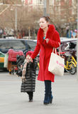 Snap portrait of a mother. Ayong mother in red coat is walking and leading her child Royalty Free Stock Photography
