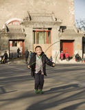 Snap portrait of a playing boy. A boy in opening coat is rope skipping on ground happily before Gulou Building in Beijing,China Stock Image