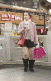 Snap portrait of a sightseeing girl. A traveling girl in bright coat and short skirt is shopping and sightseeing at Houhai lake near ancient Gulou Building in stock images