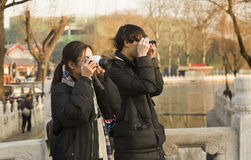 Snap portrait of a traveling couple. A yong couple in dark coat are sightseeing and taking picture on Yinding Bridge over Houhai lake near famous Gulou Street in royalty free stock photography