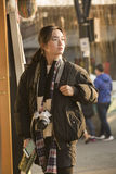 Snap portrait of a traveling girl. A girl in coat is sightseeing and waiting at a shop door and is snapped soon when her head turning to sunshine at Houhai lake stock photos