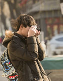 Snap portrait of traveling photographer. A man traveler in coat is taking picture at Houhai lake near famous Gulou Street in Beijing, China stock photos