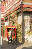 Snap portrait of a tricycle driver. A senior tricycle driver in traditional clothes is waiting for traveler for sightseeing under ancient house near famous Gulou royalty free stock images