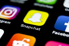 Snapchat在苹果计算机iPhone x智能手机屏幕特写镜头的应用象 Snapchat app象 社会媒介象 3d网络照片回报了社交 库存照片