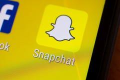 Snapchat应用在一个机器人智能手机的指图商标 免版税库存图片