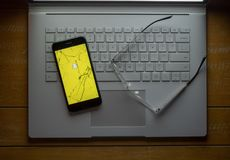 Snapchat app op een gebroken zitting van de celtelefoon op laptop naast stock afbeeldingen