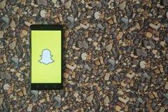 Snapchat-Logo auf Smartphone auf Hintergrund von kleinen Steinen Stockfoto