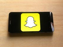 Snapchat on mobile phone. Snapchat app on smartphone kept on wooden table stock photography