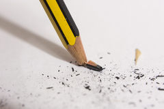 Snapped and broken pencil tip on a paper. Close up of a pencil tip which is snapped against a paper Royalty Free Stock Photos
