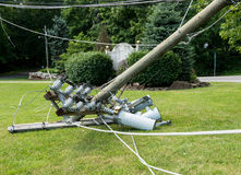 Snapped and downed power post and line after storm. Broken snapped wooden power line post with electrical components on the ground after a storm Royalty Free Stock Images