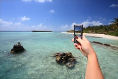 Snapshot. Maldives woman with mobile phone taking snapshot Stock Image
