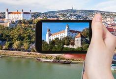 Snapshot of Bratislava Castle over Danube River. Travel concept - tourist snapshot of Bratislava Hrad Castle over Danube River waterfront on smartphone Stock Image