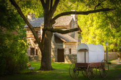 A Snapshot of the Past. An old log cabin adorned with a bench, a light pole, a huge tree, and a covered wagon make this scene from the past believable at Spring Royalty Free Stock Photo