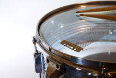Snare drum and drumsticks. Detail of a snare drum (upside down) with drumsticks resting on it Stock Image