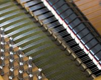 Snares pins and mutes inside old bechstein grand piano. Closeup of snares pins and mutes inside old bechstein grand piano Royalty Free Stock Image