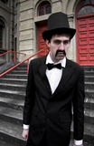 Snarling Top Hat Man. Man Dressed In His Sunday Best Stands Snarling In Top Hat And Bow Tie Outside A 19th Century Church Stock Photo