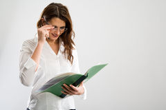 To the glasses. Businesswoman smiling while proofing something in a green folder stock photography