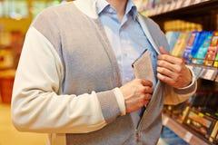 Snattare som stjäler choklad i supermarket Royaltyfri Foto