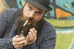 Snazzy Bearded Man. Lights a cigarette on a city street Royalty Free Stock Image