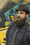 Snazzy Bearded Man. Smokes a cigarette on a city street Royalty Free Stock Photos