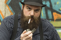 Snazzy Bearded Man. Smokes a cigarette on a city street Stock Image