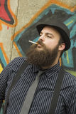 Snazzy Bearded Man. Smokes a cigarette on a city street Royalty Free Stock Photo